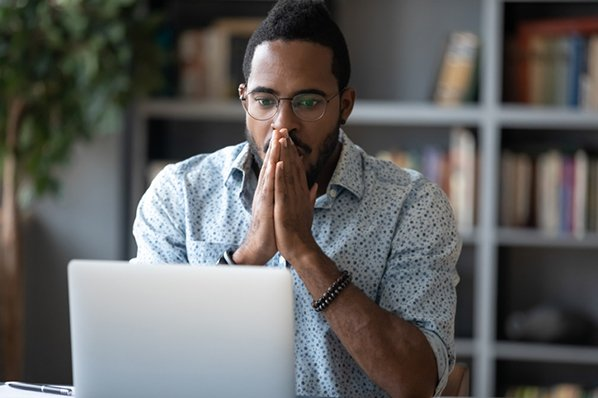 Marketer with a shocked expression at his laptop because he accidentally posted the wrong thing on Facebook