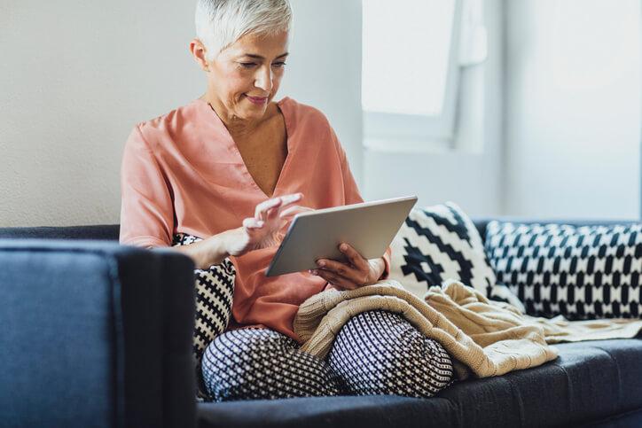 Frau-sitzt-auf-dem-Sofa-und-sucht-nach-digitalen-Produkten