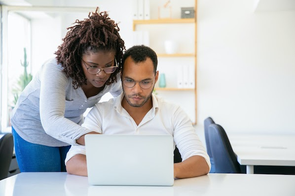 two people using a computer to park a domain name
