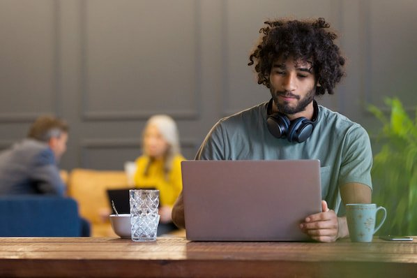 man using a laptop computer to browser for wordpress forum plugins
